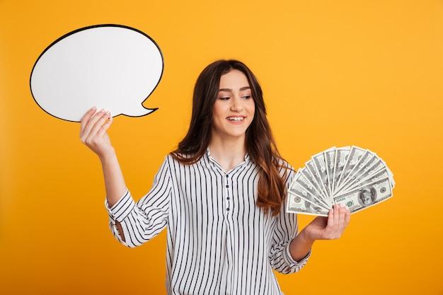 Mulher sorridente na camisa segurando dinheiro e balão em branco