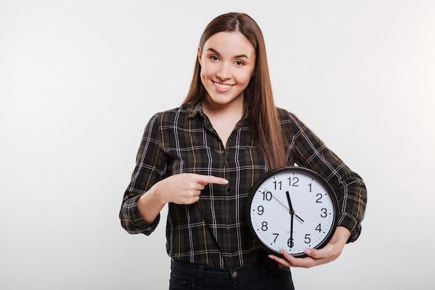Mulher sorridente na camisa, segurando o relógio