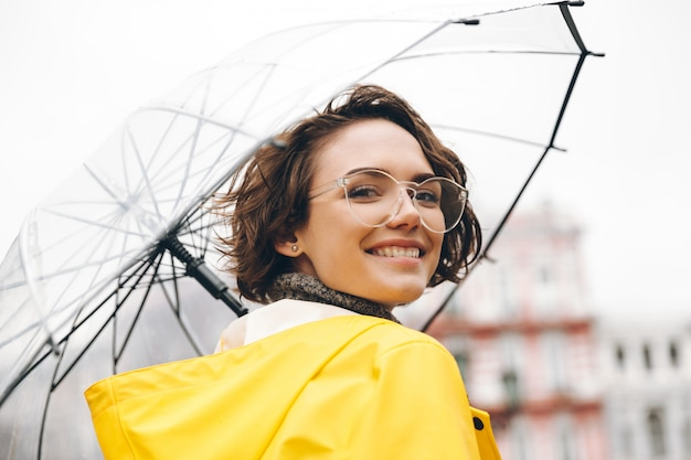 Mulher sorridente na capa de chuva amarela e óculos, tendo prazer em caminhar pela cidade sob o grande guarda-chuva transparente durante o dia chuvoso frio