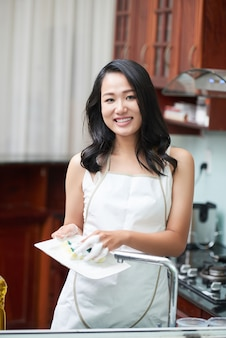 Mulher sorridente na cozinha lavando pratos