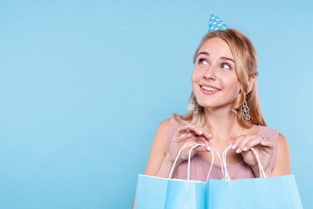 Mulher sorridente na festa de aniversário, segurando sacos com presentes