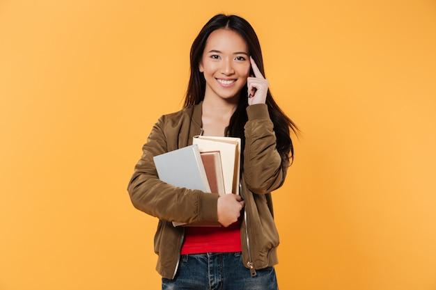 Mulher sorridente na jaqueta segurando livros enquanto olha para a câmera