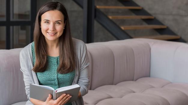 Mulher sorridente na leitura do sofá