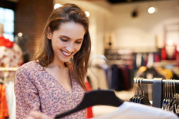Mulher sorridente na loja de roupas