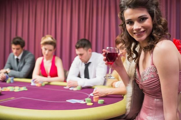 Mulher sorridente na mesa de poker
