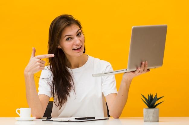 Mulher sorridente na mesa segurando e apontando para laptop