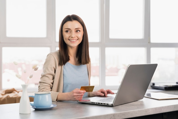 Mulher sorridente na mesa trabalhando no laptop