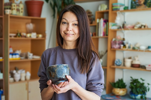 Mulher sorridente na oficina segurando uma tigela de barro. o mestre mostra seu trabalho.