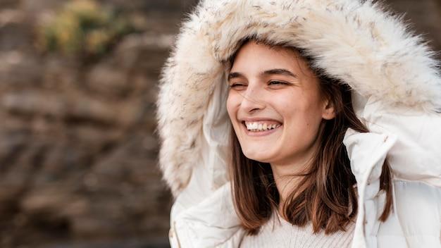 Mulher sorridente na praia com jaqueta de inverno e espaço de cópia
