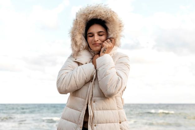 Mulher sorridente na praia com jaqueta de inverno