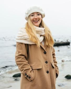 Mulher sorridente na praia no inverno
