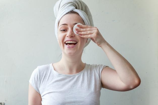 Mulher sorridente na toalha na cabeça com remoção de pele macia saudável compõem com almofada de algodão isolada na parede branca