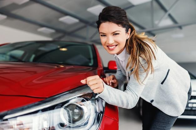 Mulher sorridente, negociante de automóveis, parada no salão de automóveis, esfregando os faróis com a manga