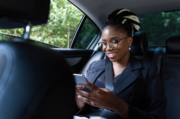 Mulher sorridente no banco de trás do carro olhando para o tablet