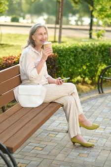Mulher sorridente no banco do parque tomando café