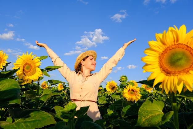 Mulher sorridente no chapéu de palha no campo de girassol desabrocham