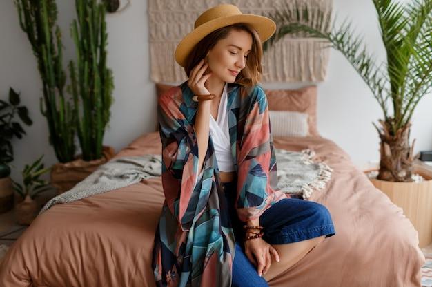 Mulher sorridente no chapéu de palha relaxando em casa no interior acolhedor boho