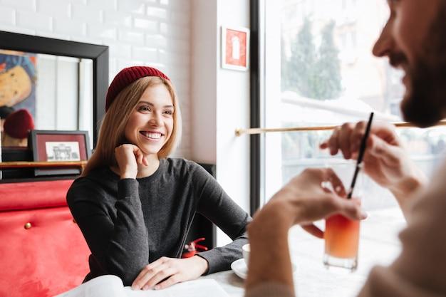 Mulher sorridente no chapéu vermelho falando com homem