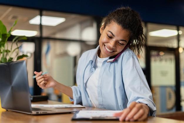 Mulher sorridente no escritório usando laptop e falando em smartphone