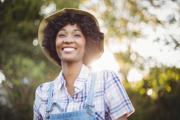 Mulher sorridente no jardim olhando para longe