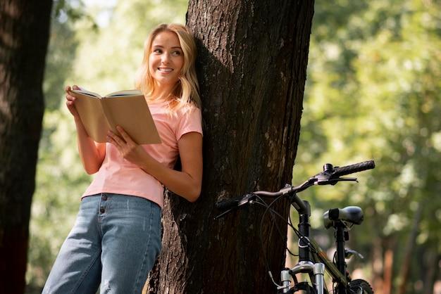 Mulher sorridente no parque com sua bicicleta lendo