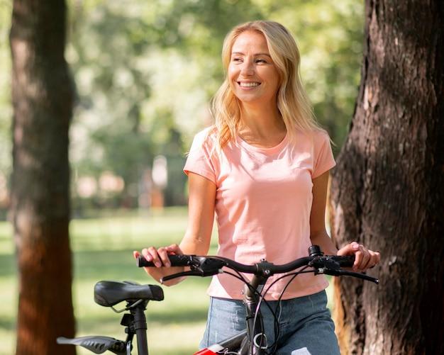 Mulher sorridente no parque com sua bicicleta