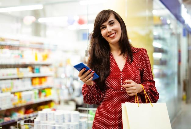 Mulher sorridente no shopping com smartphone e sacolas de compras