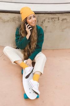 Mulher sorridente no skate falando por telefone