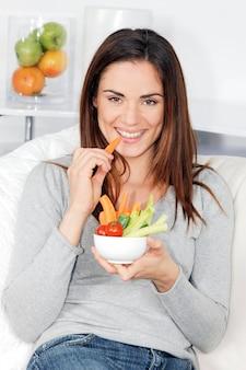 Mulher sorridente no sofá com salada de legumes