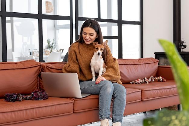 Mulher sorridente no sofá segurando seu cachorro