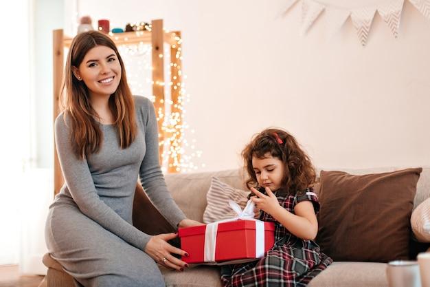 Mulher sorridente no vestido dando um presente para a criança. aniversariante posando com a mãe.
