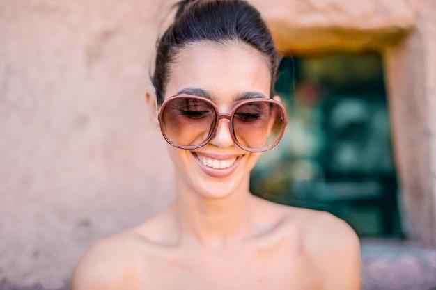 Mulher sorridente, óculos sol cansativo