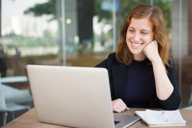 Mulher sorridente olhando a tela do laptop no café