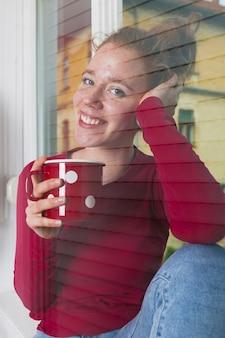 Mulher sorridente, olhando através da janela e desfrutar de café