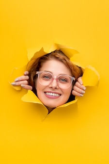 Mulher sorridente olhando através de pôster rasgado