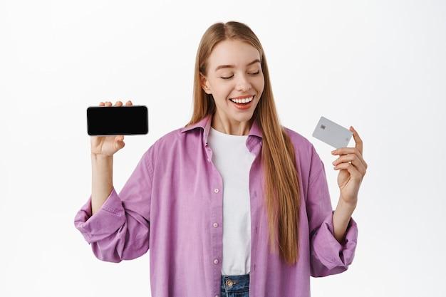 Mulher sorridente, olhando feliz para o cartão de crédito, mostrando a tela horizontal do smartphone, aplicativo recomendado ou loja da internet, em pé sobre uma parede branca