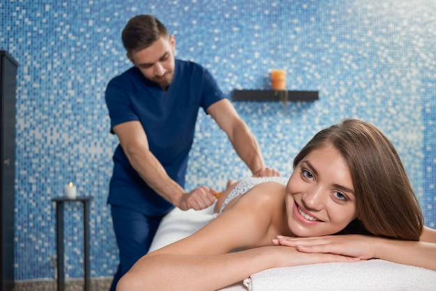 Mulher sorridente, olhando para a câmera durante massagem crioula no spa