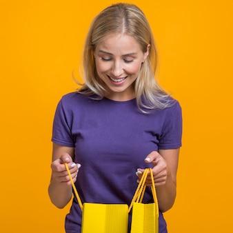 Mulher sorridente olhando para as sacolas de compras
