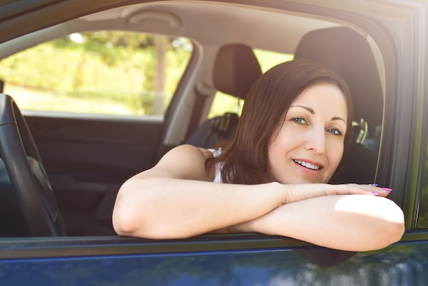 Mulher sorridente, olhando para fora do carro. um retrato de uma mulher sorridente, sentada no carro, olhando para a câmera.