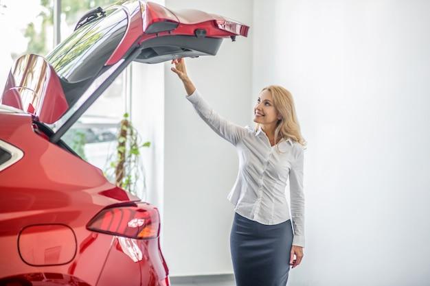 Mulher sorridente olhando para o porta-malas aberto do carro