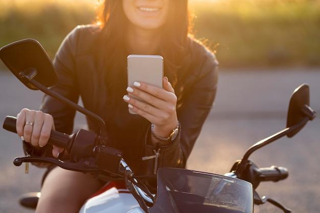 Mulher sorridente olhando para o smartphone enquanto está sentada em sua motocicleta