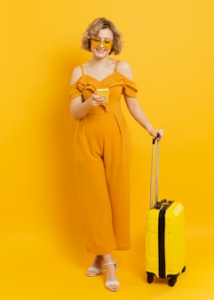 Mulher sorridente, olhando para o smartphone, segurando a bagagem