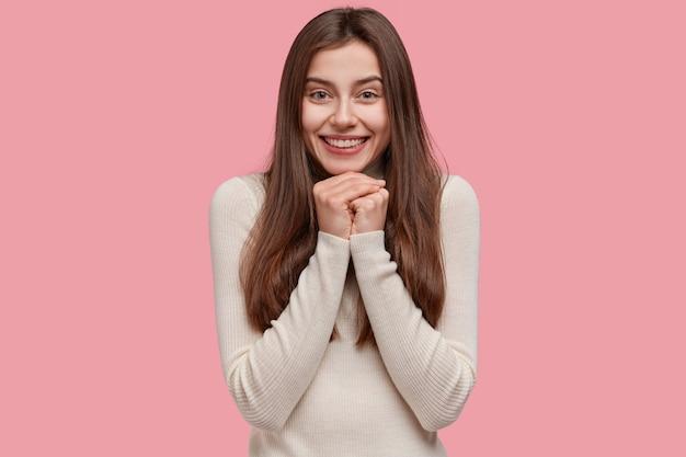 Mulher sorridente otimista aperta as mãos perto do rosto, sorri amplamente e tem uma aparência charmosa