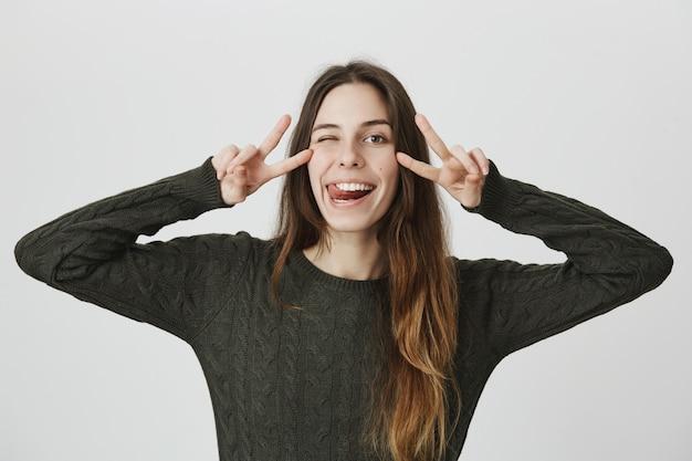 Mulher sorridente otimista na camisola, mostrando a língua e o sinal de paz, piscadela despreocupada