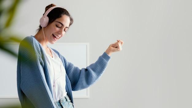 Mulher sorridente ouvindo música em fones de ouvido com espaço de cópia