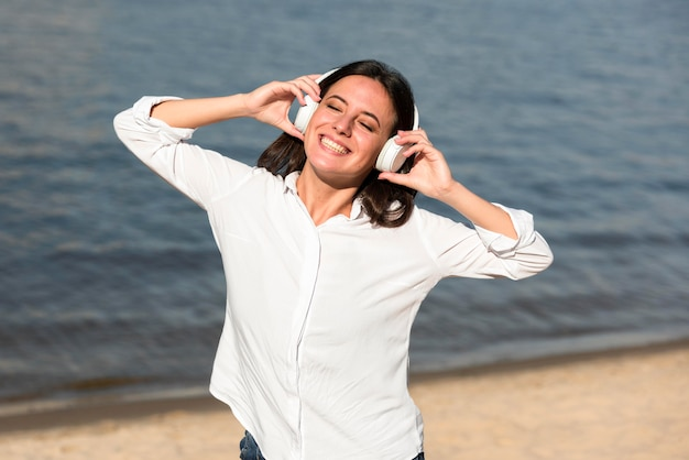 Mulher sorridente ouvindo música em fones de ouvido na praia