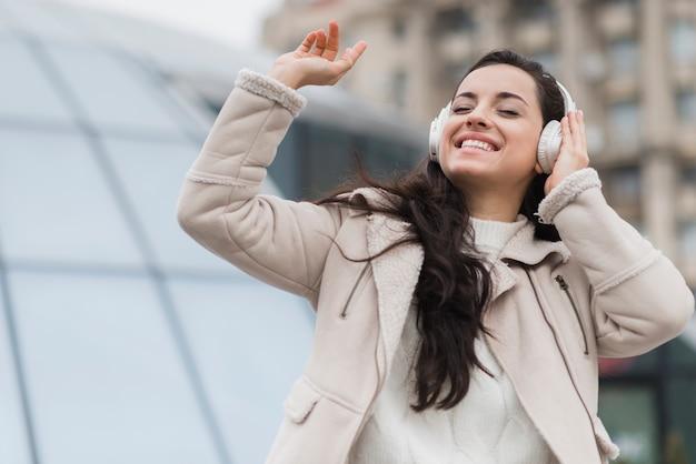 Mulher sorridente, ouvindo música em fones de ouvido