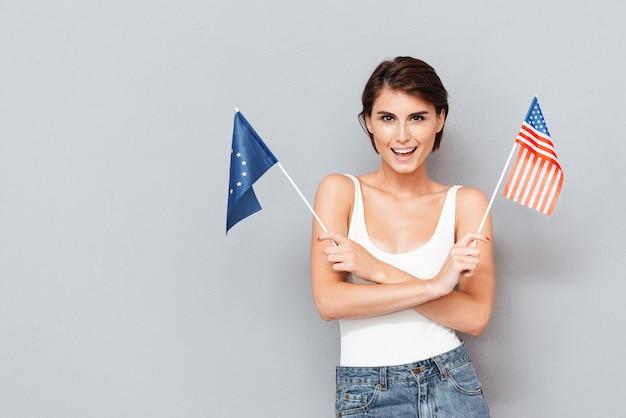 Mulher sorridente patriótica segurando bandeiras da europa e dos eua sobre um fundo cinza