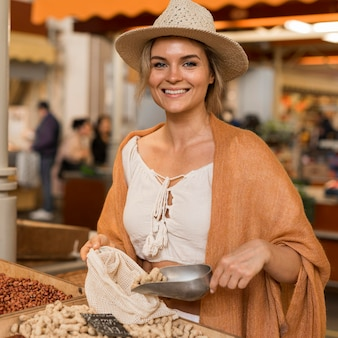 Mulher sorridente pegando comida desidratada no mercado