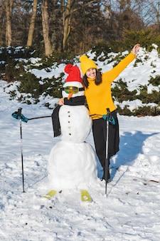 Mulher sorridente perto do espaço da cópia do boneco de neve esquiador